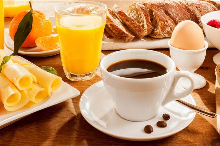 Breakfast table with coffee, pastries, muesli, eggs, fruit and juice in detail