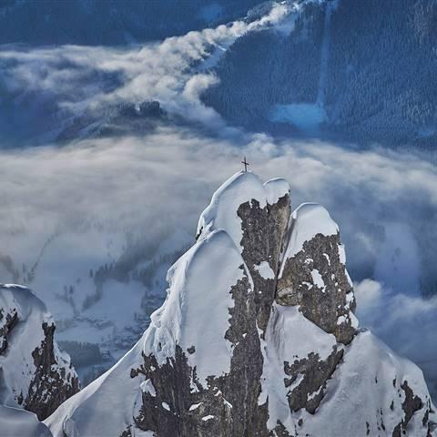 Bergspitze mit Gipfelkreuz im Winter