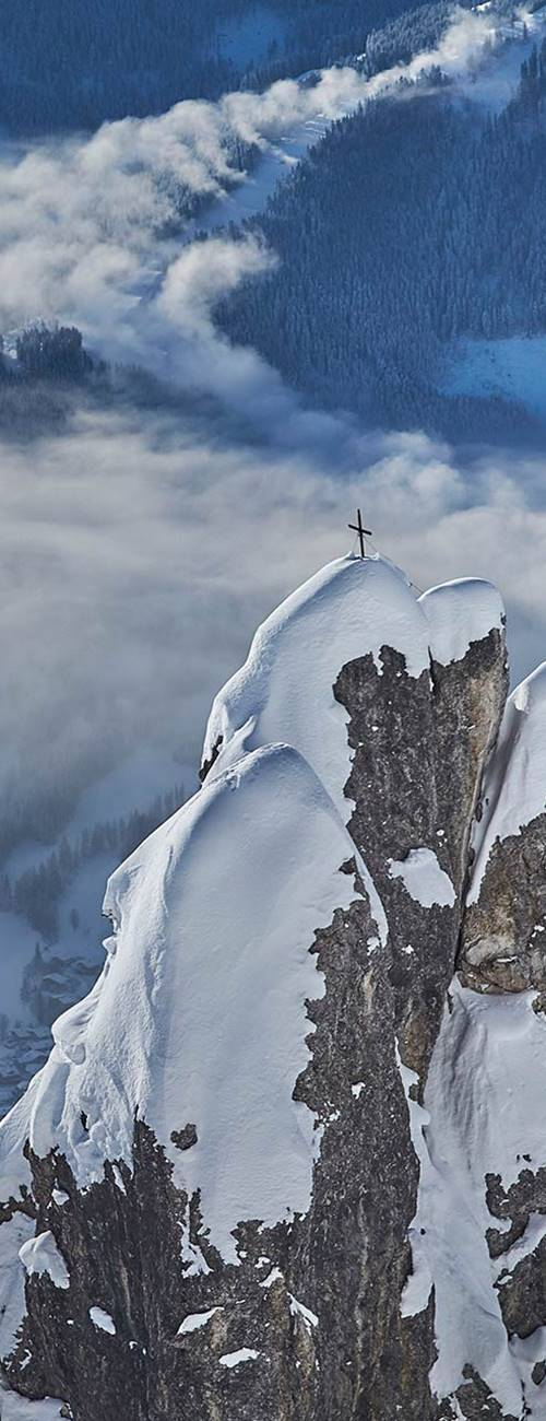 mountain with summit cross in winter