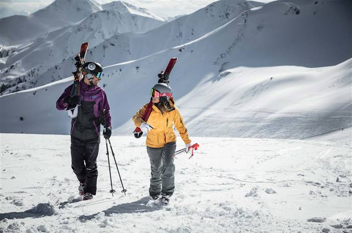 Two skiers carry their skis over their shoulders